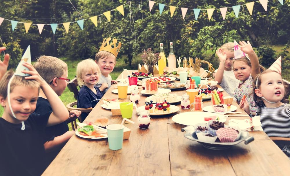 Enfants en train de fêter un anniversaire dans le jardin pendant le goûter.